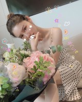 Carina Zhang uploads a picture of herself with a large bouquet of flowers